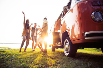 summer holidays, road trip, vacation, travel and people concept - smiling young hippie friends having fun over minivan car