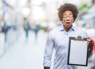 Afro american man holding clipboard over isolated background scared in shock with a surprise face, afraid and excited with fear expression