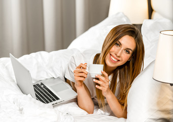 attractive young caucasian cmiling cheerful woman at home in bed with cup of tea or coffee with notebook laptop looking at camera working at home