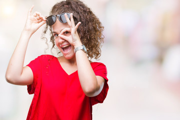 Beautiful brunette curly hair young girl wearing sunglasses over isolated background doing ok gesture with hand smiling, eye looking through fingers with happy face.