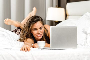 attractive young caucasian cmiling cheerful woman at home in bed with cup of tea or coffee with notebook laptop looking at notebook working at home