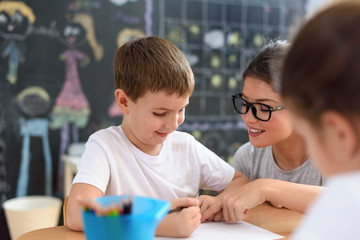 Preschool teacher looking at smart child learning to write and draw. Early education. Harnessing...