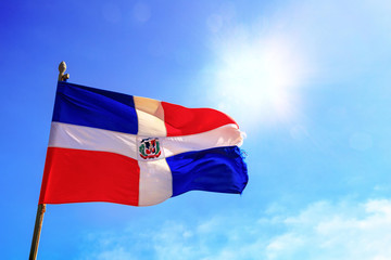 The flag of the Dominican Republic is waving before a blue sky with sunbeams. The Spanish inscription says: GOD, HOMELAND, FREEDOM
