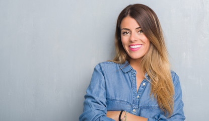 Young adult woman over grunge grey wall wearing denim outfit happy face smiling with crossed arms looking at the camera. Positive person. Wall mural