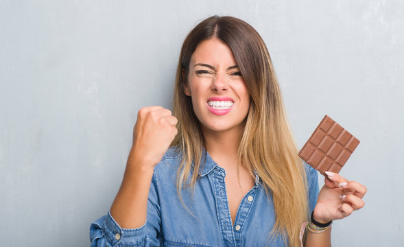 Young adult woman over grey grunge wall eating chocolate bar annoyed and frustrated shouting with anger, crazy and yelling with raised hand, anger concept