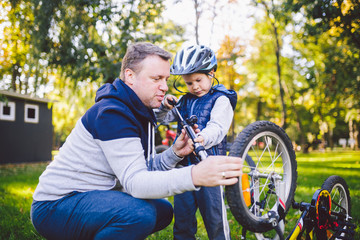 Father's day Caucasian dad and 5 year old son in the backyard near the house on the green grass on the lawn repairing a bicycle, pumping a bicycle wheel. Dad teaches how to repair a child's bike