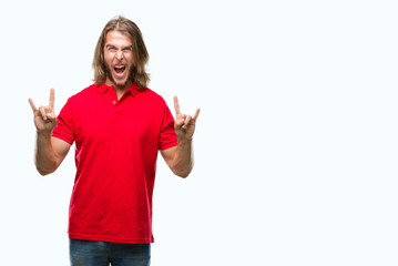 Young handsome man with long hair over isolated background shouting with crazy expression doing rock symbol with hands up. Music star. Heavy concept.