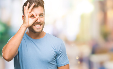 Young handsome man over isolated background doing ok gesture with hand smiling, eye looking through fingers with happy face.