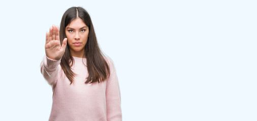 Young beautiful hispanic woman wearing a sweater doing stop sing with palm of the hand. Warning expression with negative and serious gesture on the face.