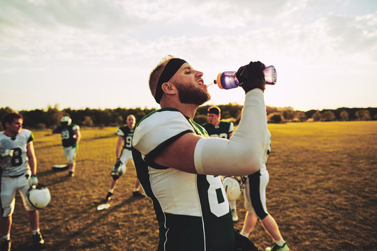 American football player drinking water during practice outside