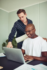 Two businessman working together on a laptop in an office