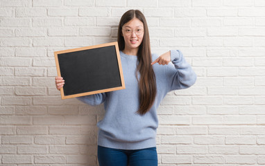 Young Chinese woman over brick wall holding blackboard with surprise face pointing finger to himself