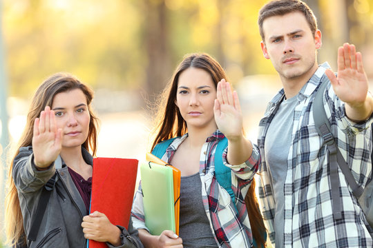 Three students gesturing stop in a park