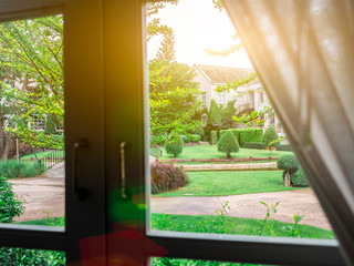 Beautiful garden Nature behind window lighting flare bright in the morning. White frame and dark handle. Look through the glass.