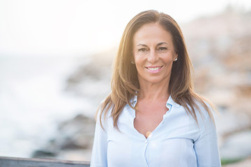 Beautiful middle age hispanic woman at the sea shore on a sunny day with a happy face standing and smiling with a confident smile showing teeth
