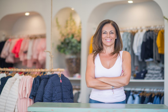 Beautiful middle age hispanic woman standing with smile on face at clothes store. Shop owner and shop assistant smiling confident and cheerful with crossed arms at desk.