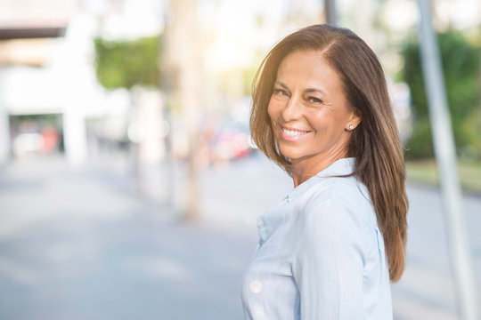 Beautiful middle age hispanic woman at the city street on a sunny day with a happy face standing and smiling with a confident smile showing teeth
