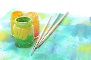 Paint bottles and paint brushs on water color paper,art equipments concept.