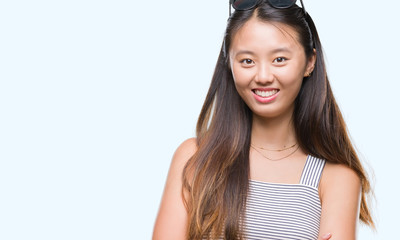 Young asian woman wearing sunglasses over isolated background happy face smiling with crossed arms looking at the camera. Positive person.