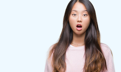 Young asian woman over isolated background afraid and shocked with surprise expression, fear and excited face.
