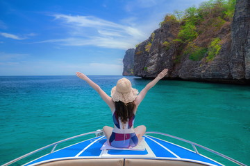 Cute girl is relaxing in the summer at the sea.Traveling by the sea.Holidays in the summer.Beautiful sea of Thailand.