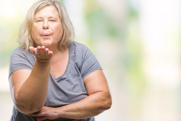 Senior plus size caucasian woman over isolated background looking at the camera blowing a kiss with hand on air being lovely and sexy. Love expression.