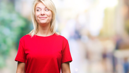 Young beautiful blonde woman wearing red t-shirt over isolated background smiling looking side and staring away thinking.