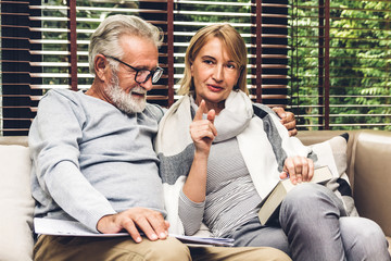 Senior couple relax talking and reading newspaper together on sofa in living room at home.Retirement couple concept