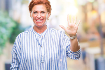 Atrractive senior caucasian redhead woman over isolated background showing and pointing up with fingers number five while smiling confident and happy.