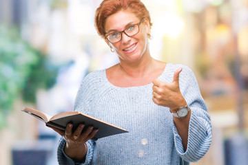 Senior caucasian woman reading a book over isolated background happy with big smile doing ok sign, thumb up with fingers, excellent sign