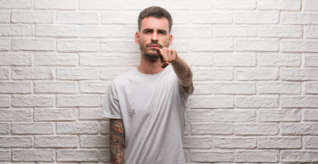 Young adult man standing over white brick wall pointing with finger to the camera and to you, hand sign, positive and confident gesture from the front