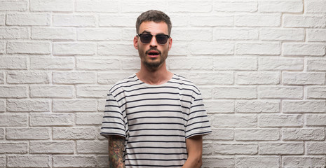 Young adult man wearing sunglasses standing over white brick wall afraid and shocked with surprise expression, fear and excited face.