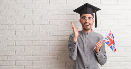 Young adult man over brick wall wearing graduation cap holding uk flag very happy and excited, winner expression celebrating victory screaming with big smile and raised hands