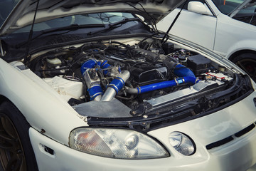 Open hood of a car with the view of the engine. Engine failure. Engine pings. Engine runs rough. A car want a repair. Vehicle unsheduled repair. Car engine preventive diagnostics. Official car checkup