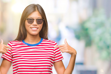 Young asian woman wearing sunglasses over isolated background looking confident with smile on face, pointing oneself with fingers proud and happy.