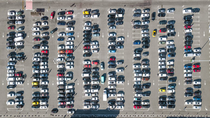 Aerial drone view of parking lot with many cars near shopping mall from above, city transportation and urban concept