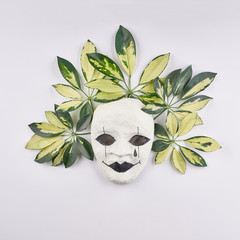 Stylized mask and tropical palm leaves on white background.