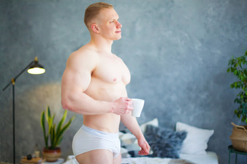 Sexy handsome young man standing shirtless in his bedroom, holding a coffee cup
