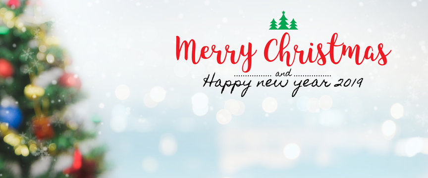 Christmas and Happy new year 2019 on blurred bokeh christmas tree banner background with snowfall.