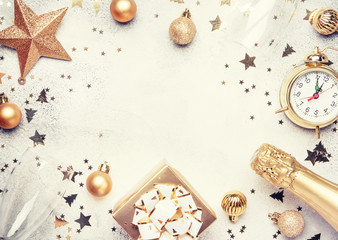 Christmas or New Year composition, frame, pink background with gold Christmas decorations, stars, snowflakes, balls, alarm clock, gift box and bottle of champagne, top view