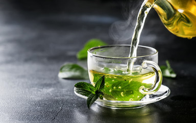 Hot chinese green tea with mint, with splash pouring from the kettle into the cup, steam rises, dark background, selective focus