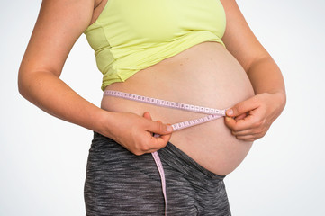 Pregnant woman is measuring belly with tape meter
