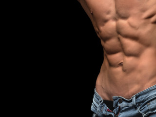 Torso of strong man in jeans against dark background. perfect abs