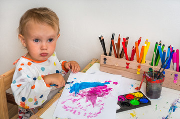 Cute baby is painting with paintbrush on paper