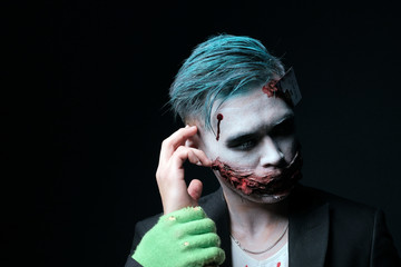 The magician guy in the image of the Joker holds his right hand with his glove. Men's makeup in the style of Halloween. Cosplay for themed show party. Bloody mouth, green hair. Black copyspace.