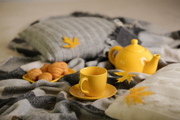 Home comfort and warmth in the autumn time. Gray plaid, knitted pillows, tea and autumn maple leaves.
