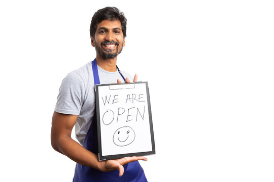 Supermarket employee holding we are open text.