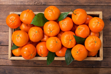 Fresh mandarin oranges fruit or tangerines with leaves in wooden box