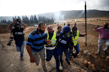 Wounded journalist, who was hit with a tear gas canister, is evacuated during clashes over an Israeli order to shut down a Palestinian school near Nablus in the occupied West Bank