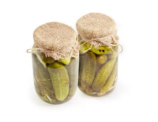 Canned cucumbers in glass jars on a white background